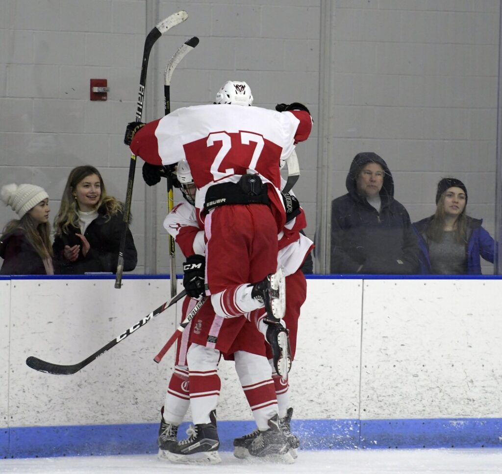 Cony's Zack Whitney leaps into the arms of his teammates after a goal against Gardiner on Thursday in Hallowell.