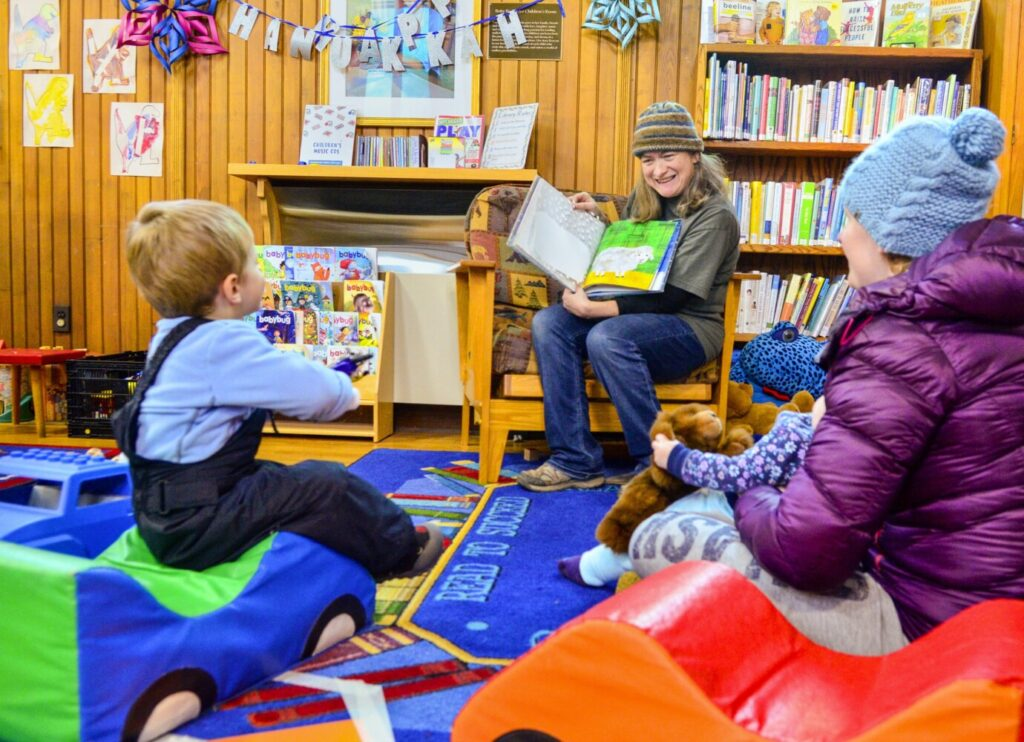 Assistant Librarian Stacie Linkel reads a book to a family during story hour Wednesday at the Hubbard Free Library in Hallowell.