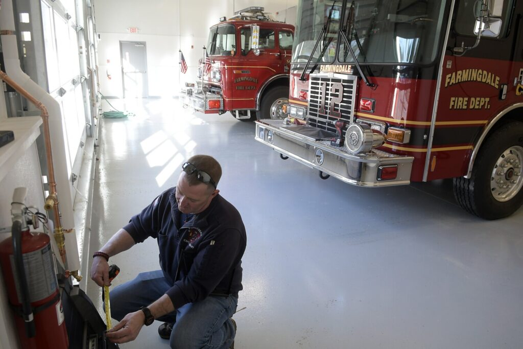 Capt. Doug Ebert hangs  a digital dispatch system Tuesday in the bays of the new Farmingdale Fire Station. Kennebec Journal photo by Andy Molloy