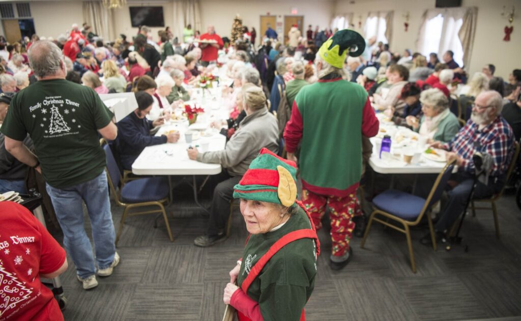 Flo Pouliott, center, waits Wednesday to serve people at the 13th annual Central Maine Family Christmas Dinner at the Elks Lodge in Waterville.