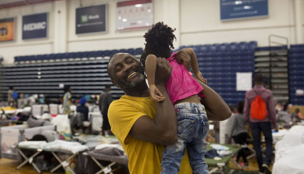 In a June 2019 photo, Coco Ikoko plays with a friend's child at the Portland Expo, where he lived temporarily with other asylum seekers from the Congo and Angola. Ikoko fled his home in the Congo after he was informed of his pending arrest because of his involvement in an underground political group. The influx of immigrants, many to Maine's biggest city, is changing the state's demographics rapidly.