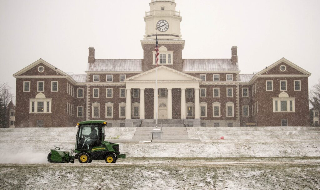 Crews clear snow from the walkway in front of Miller Library at Colby College in Waterville on Tuesday.