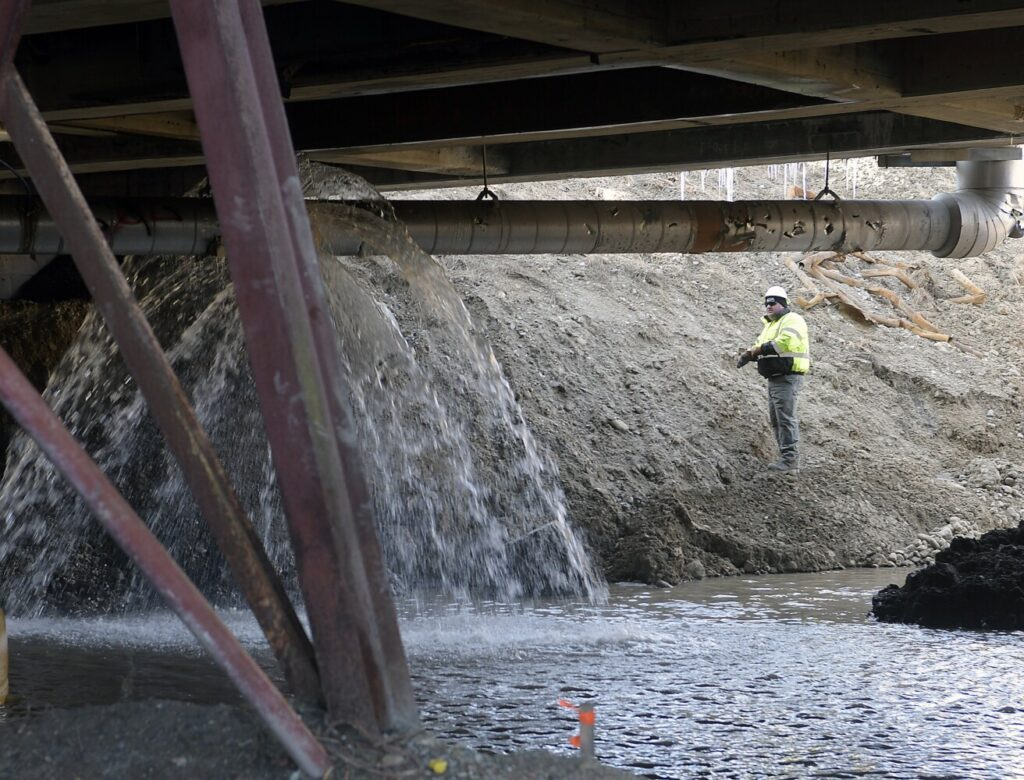 A worker examines a water main that ruptured Thursday beneath the Bridge Street bridge in Gardiner. Witnesses said an excavator that was working accidentally hit the water pipe, flooding the area beneath the bridge. The construction is part of a Maine Department of Transportation project to rebuild both bridges in Gardiner spanning Cobbossee Stream.