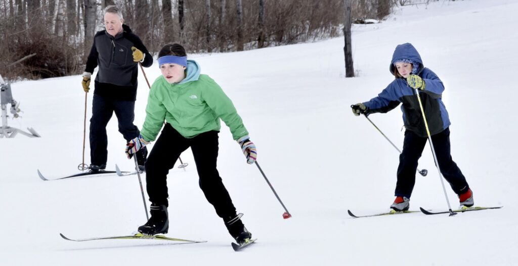 Maeve Lakin, center, and her brother John race on cross-country skies on trails at the popular Quarry Road Recreation Area in Waterville last year.