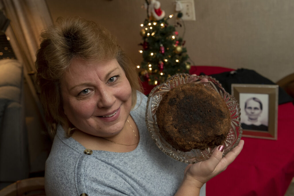 Julie Ruttinger of Tecumseh, Mich., holds a 141-year-old fruitcake, a family heirloom baked by her great-great-grandmother, Fidelia Ford, in 1878. Fidelia, pictured at left, died before the cake was served and the family, out of respect of her memory, decided not to eat it and has instead passed it down for generations.