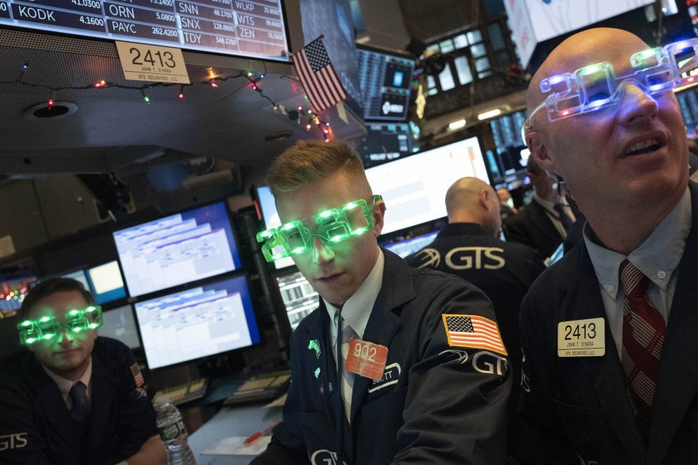 Stock traders wear New Year's 2020 party glasses at the New York Stock Exchange on Tuesday.