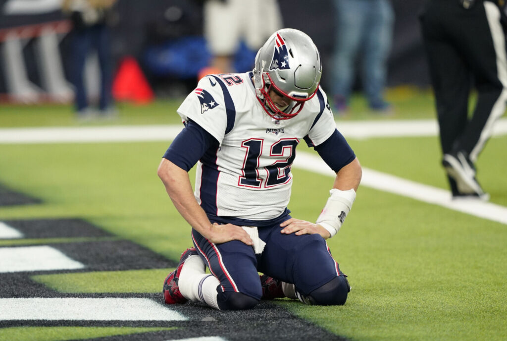 Patriots quarterback Tom Brady kneels on the turf after a play during the second half of New England's 28-22 loss to the Houston Texans on Sunday in Houston.