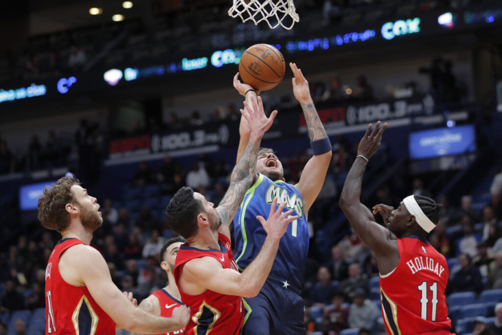 Luka Doncic, center, shoots between New Orleans defenders Nicolo Melli, left, and JJ Redick and Jrue Holiday during's Tuesday's game.