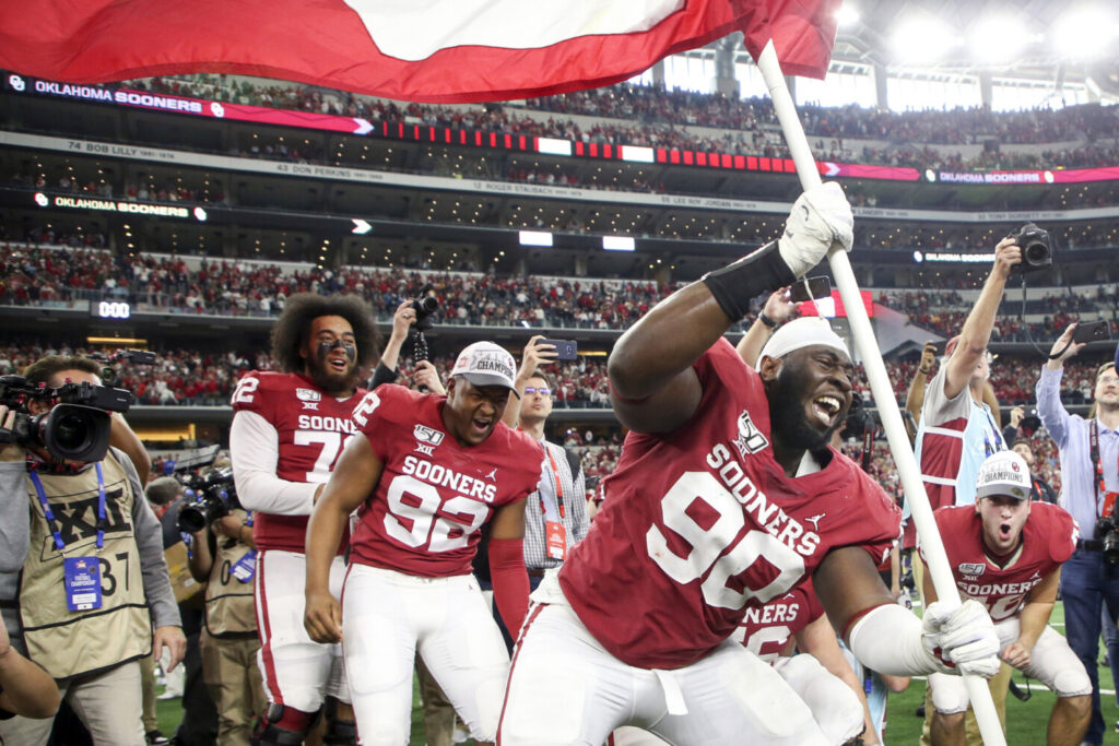 Oklahoma defensive lineman Neville Gallimore plants a University of Oklahoma flag after the Sooners' 30-23 overtime win over Baylor in for the Big 12 Conference championship game on Saturday in Arlington, Texas.