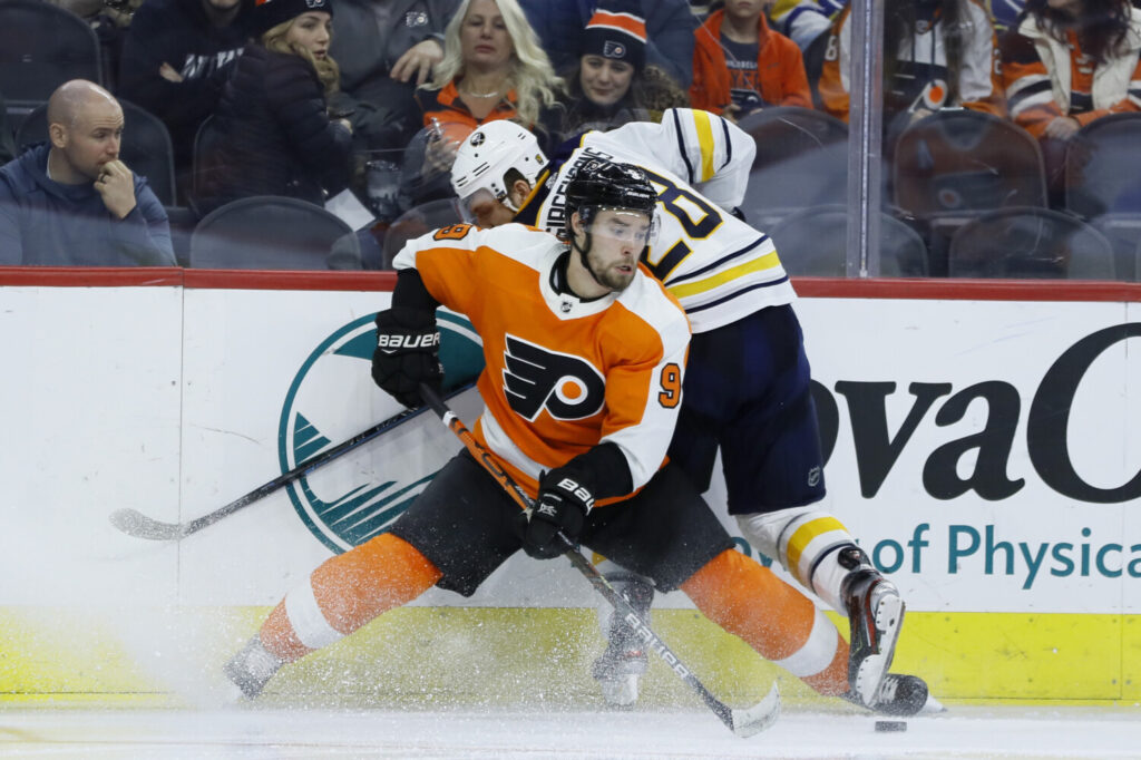 Philadelphia's Ivan Provorov, front, battles for the puck against Buffalo's Zemgus Girgensons during the third period Thursday in Philadelphia.