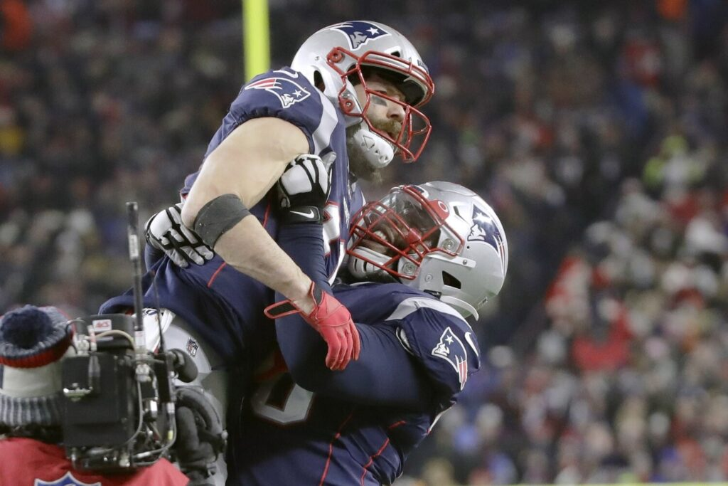 New England Patriots wide receiver Julian Edelman, top, gets a lift from offensive tackle Isaiah Wynn after catching a pass for a two-point conversion in the fourth quarter of the Patriots' 24-17 win over Buffalo on Saturday in Foxborough, Mass.