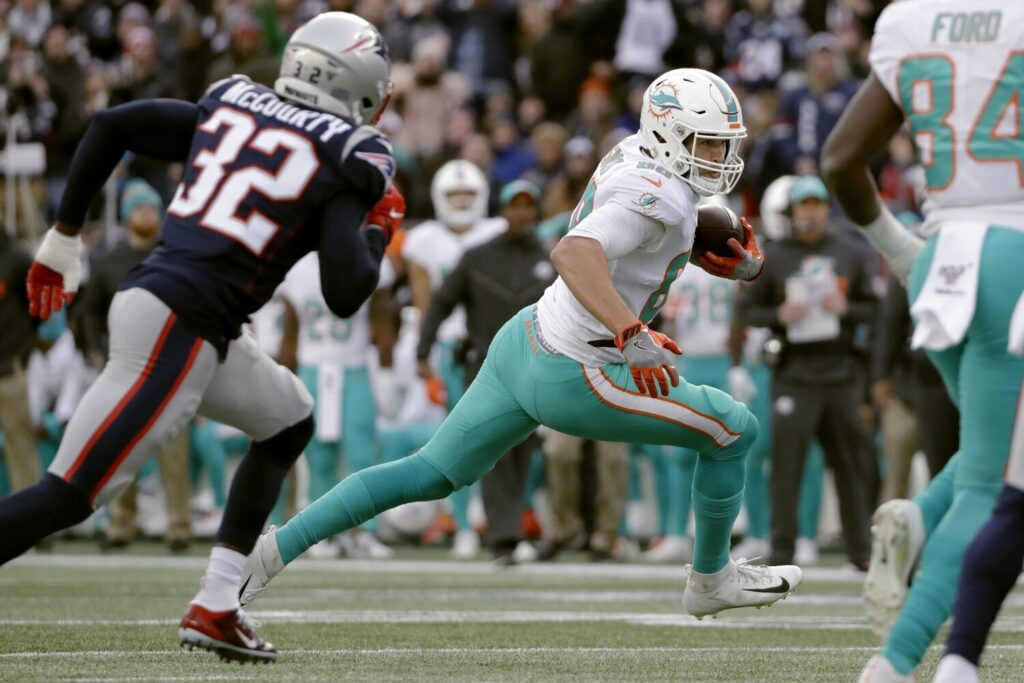 Miami Dolphins tight end Mike Gesicki runs from New England Patriots safety Devin McCourty, left, after catching a pass in the second half of the Dolphins' 27-24 win Sunday in Foxborough, Mass.