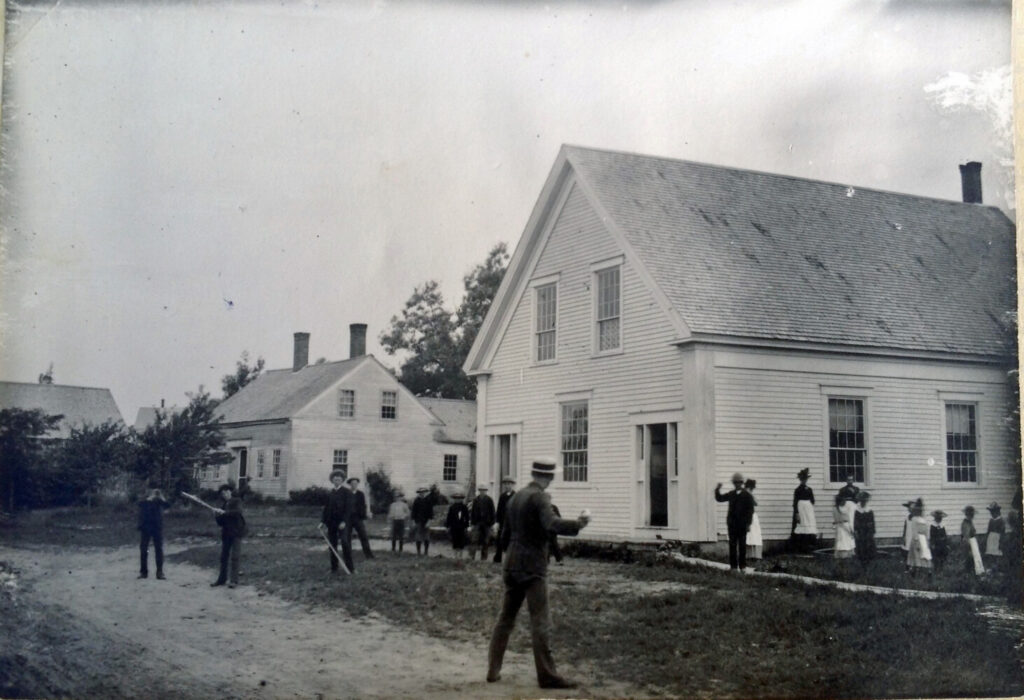 In this early 1800 photo, teacher Charles Besse plays ball with students at the original Jefferson Village School. Notice that the bats are boards and there are no gloves to be seen. The girls, most with hats and aprons, look on. The building still stands in the North Village across from the apartment building which used to be Hoffses and later, Marshall Holmes's store.