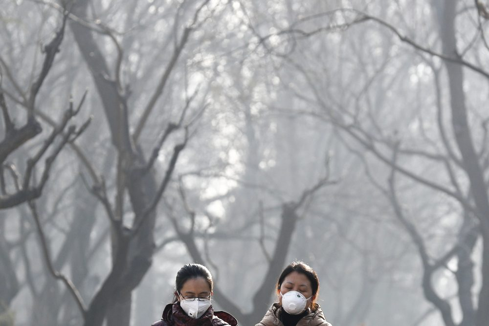 FILE - In this Dec. 19, 2016, file photo, women wearing masks to protect themselves from air pollution walk through Ritan Park shrouded by dense smog in Beijing. Scientists say emissions worldwide need to start falling sharply from next year if there is to be any hope of achieving the Paris climate accord's goal of capping global warming at 1.5 degrees Celsius (2.7 Fahrenheit). (AP Photo/Andy Wong, File)