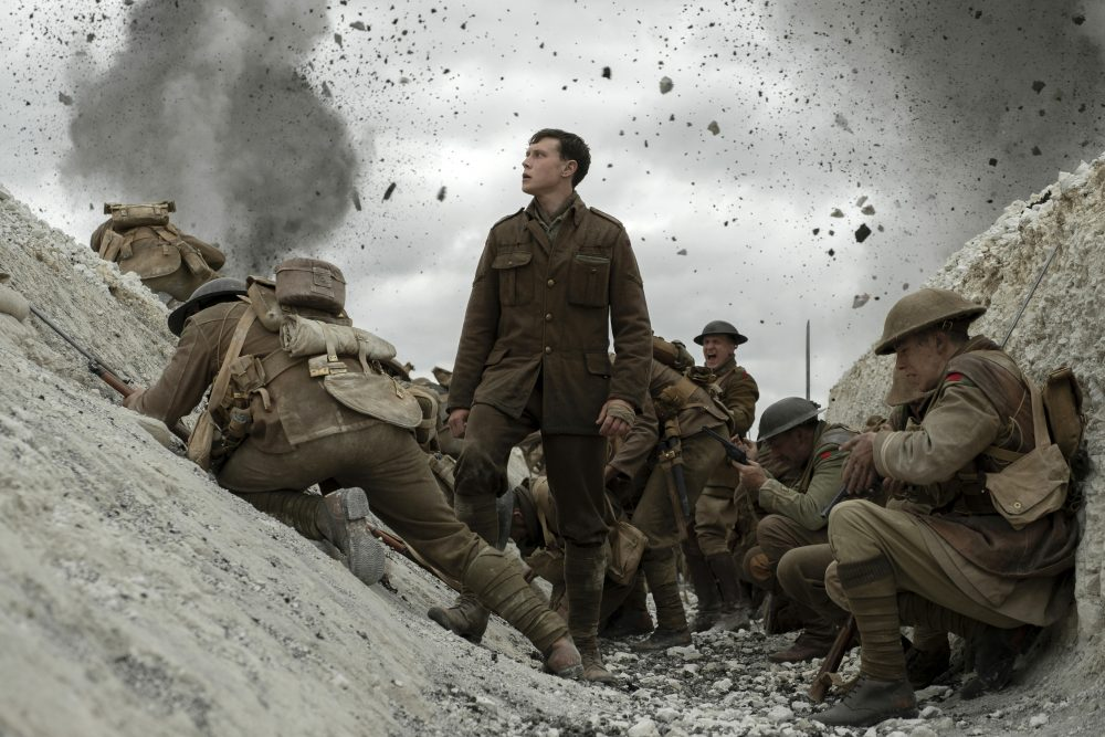 """This image released by Universal Pictures shows George MacKay, center, in a scene from """"1917,"""" directed by Sam Mendes."""