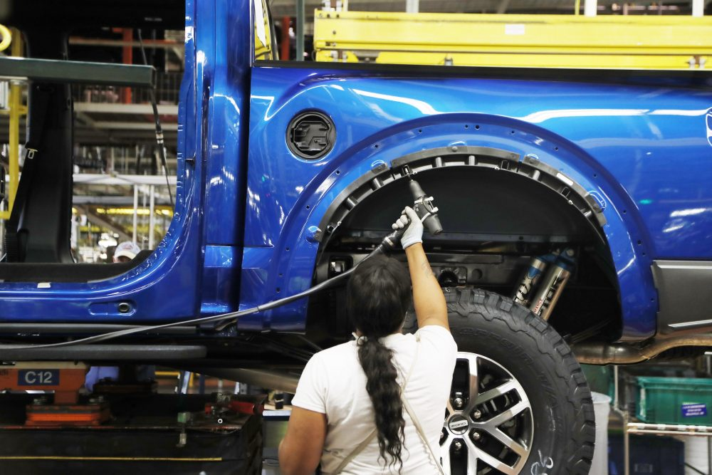 An assemblyman works on a 2018 Ford F-150 truck at the Ford Rouge assembly plant, in Dearborn, Mich., last year. Ford Motor Co. is investing $1.45 billion to build new pickup trucks, SUVs, and electric and autonomous vehicles. At the Dearborn truck plant, $700 million will be invested.