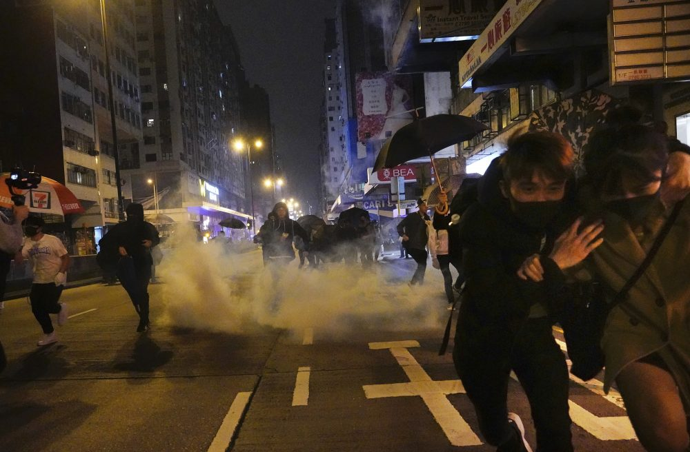 Protesters react as police fire tear gas during a demonstration in Hong Kong early Wednesday.