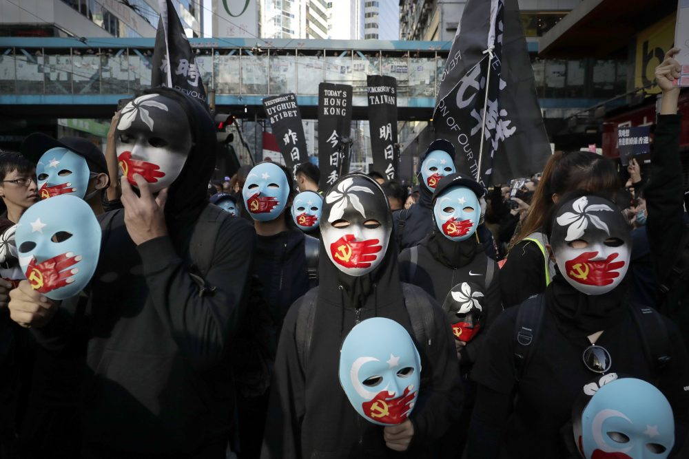Masked pro-democracy protesters march Sunday in Hong Kong, marking six months of demonstrations.