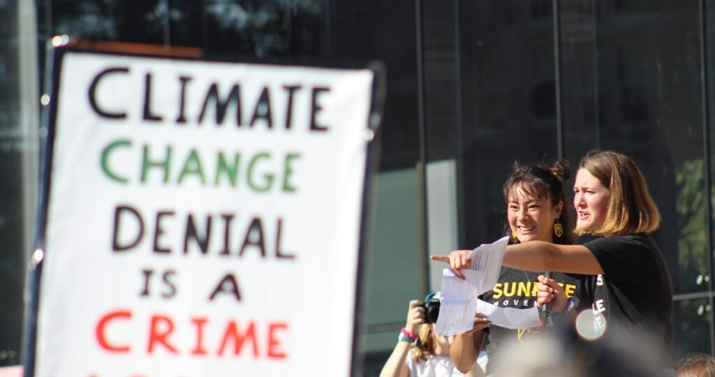 """Bowdoin College students Ayana Harscoet (left) and Perrin Milliken lead protesters in a song at Bowdoin College in September.  Students protested  and demanded justice and change in the face of what they called a """"climate crisis."""