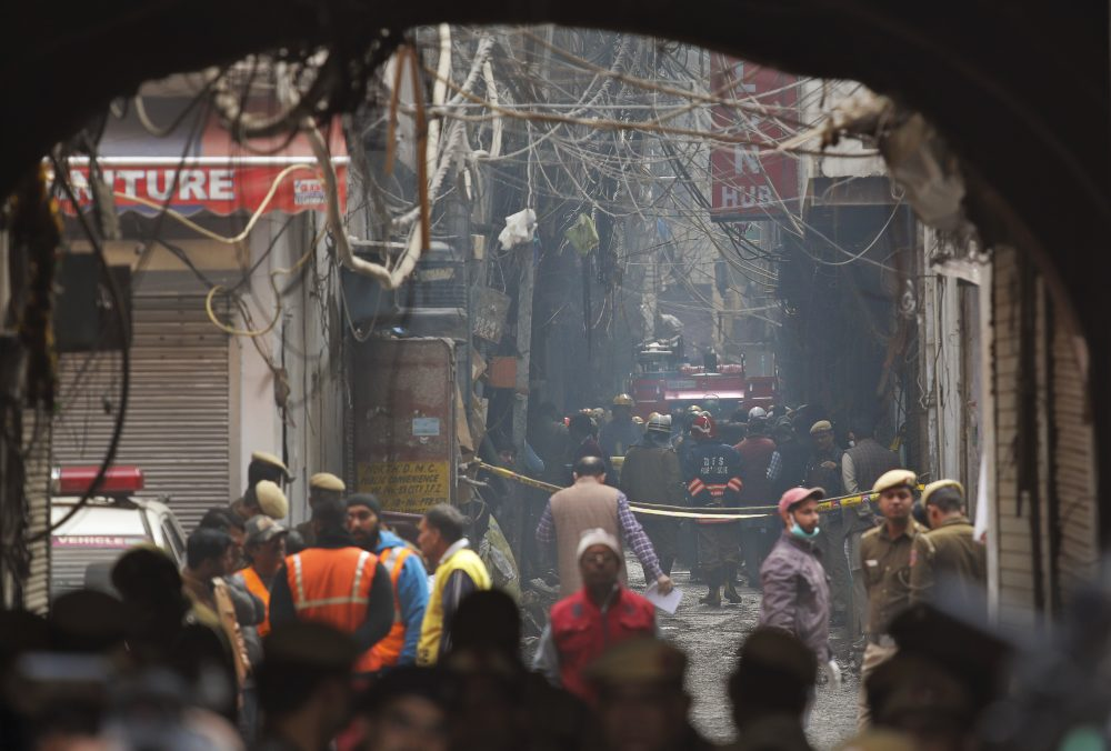 A fire engine stands by the site of a fire Sunday in an alleyway, tangled in electrical wire and too narrow for vehicles to access, in New Delhi, India. Dozens of people died on Sunday in a devastating fire at a building in a crowded grains market area in central New Delhi, police said.