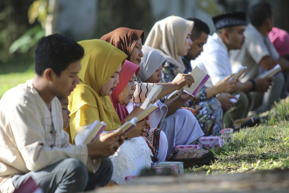 People read the Quran as they pray at a mass gravesite for the victims of the Indian Ocean tsunami, during the commemoration of the 15th anniversary of the disaster in Banda Aceh, Indonesia, on Thursday.