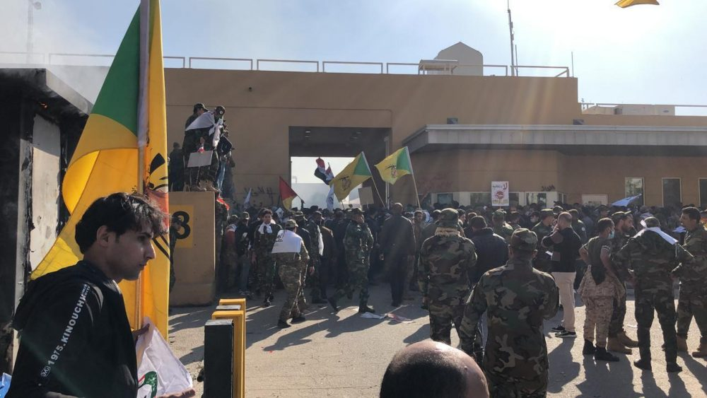 Dozens of Iraqi Shiite militia supporters gather outside the U.S. embassy compound in Baghdad, Iraq, on Tuesday. An angry mob smashed a door and stormed into the compound Tuesday after deadly U.S. airstrikes Sunday against the Kataeb Hezbollah militia in Iraq and Syria.