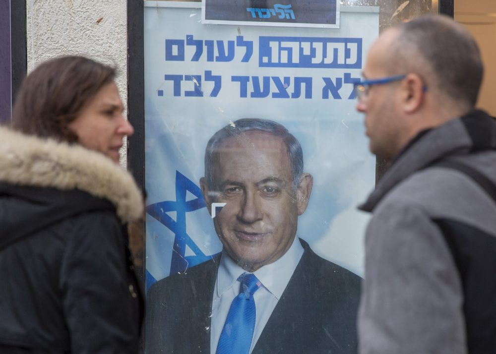 People look at a poster of Israel Prime Minister and governing Likud party leader Benjamin Netanyahu at a voting center in the northern Israeli city of Hadera, on Thursday. Netanyahu won the primary election, retaining control of his party.