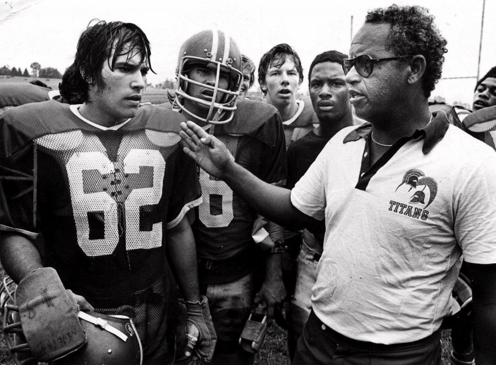 """T.C. Williams High School football coach Herman Boone, right, during a break at summer camp, with guard Johnny Colantuoni, (62) and John Vaughn, center. Boone, the Alexandria, Va., high school football coach who inspired the movie """"Remember the Titans,"""" has died."""