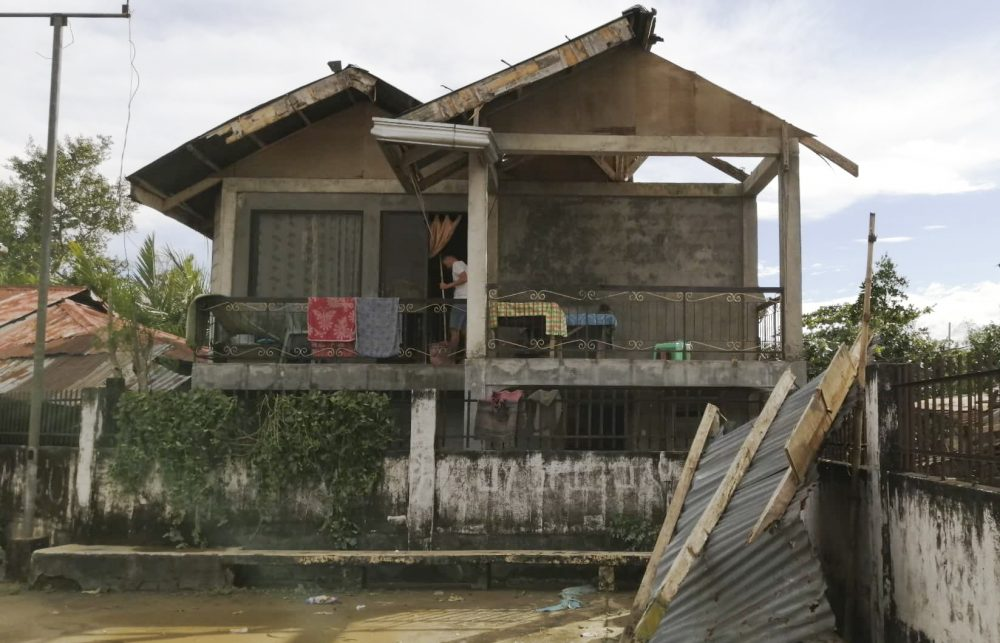 A resident checks his home damaged by Typhoon Phanfone in Ormoc city, central Philippines, on Thursday.