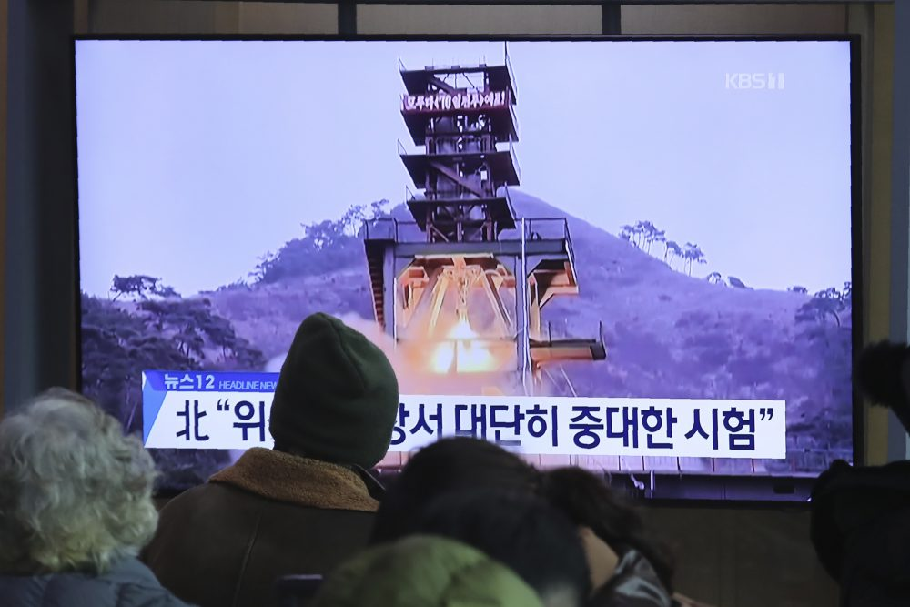 "People watch a TV screen showing a file image of a ground test of North Korea's rocket engine during a news program at the Seoul Railway Station in Seoul, South Korea,  on Dec. 9. North Korea said Sunday it carried out a ""very important test"" at its long-range rocket launch site that it reportedly rebuilt after having partially dismantled it after entering denuclearization talks with the United States last year."