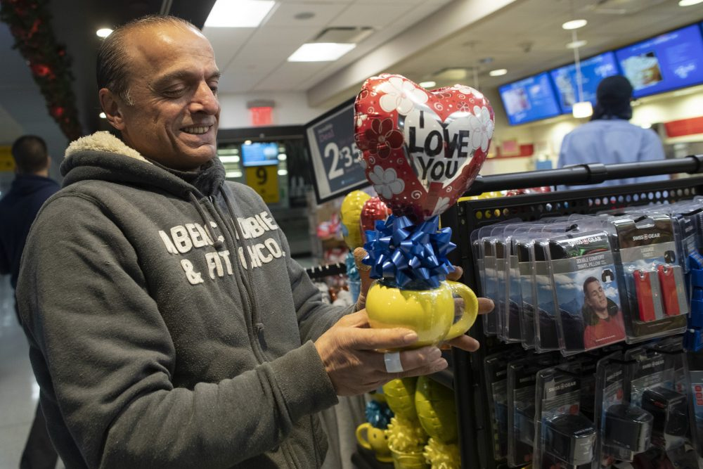 Mohammed Hafar buys a gift for his daughter Jana Hafar while waiting for her flight at JFK airport in New York on Dec. 3. Jana had been forced by President Trump's travel ban to stay behind in Syria for months while her father, his wife and son Karim started rebuilding their lives in Bloomfield, N.J.