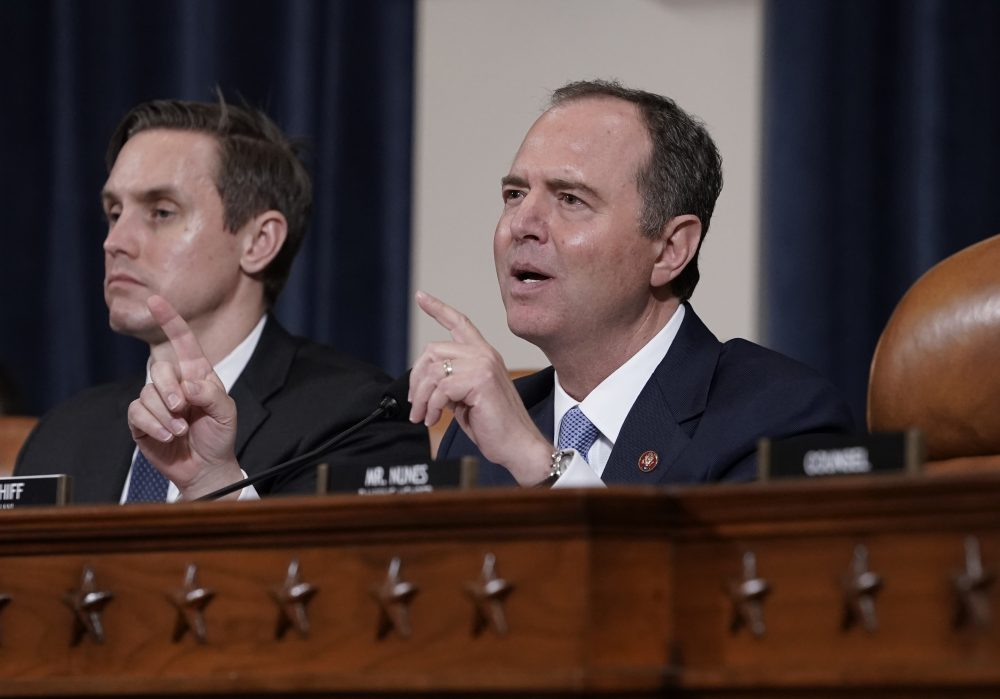 House Intelligence Committee Chairman Adam Schiff, D-Calif., with committee staffer Daniel Noble at left, makes impassioned remarks at the conclusion of a week of public impeachment hearings on President Trump's efforts to tie U.S. aid for Ukraine to investigations of his political opponents, on Capitol Hill in Washington last month. The committee released its report on Tuesday.
