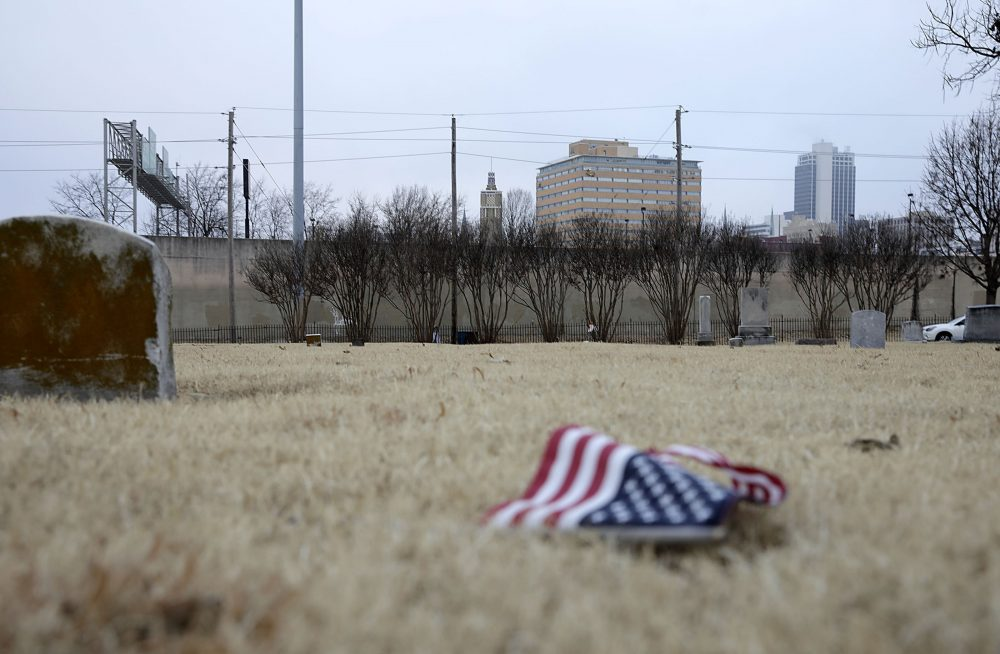 An American flag lies on the ground in front of an area of Oaklawn Cemetery. Tuesday, Dec. 17, 2019. in Tulsa, Okla.,  where a 25-by-30 foot apparent pit, consistent with a common grave, was located during initial scanning for unmarked graves related to the 1921 Tulsa Race Massacre.