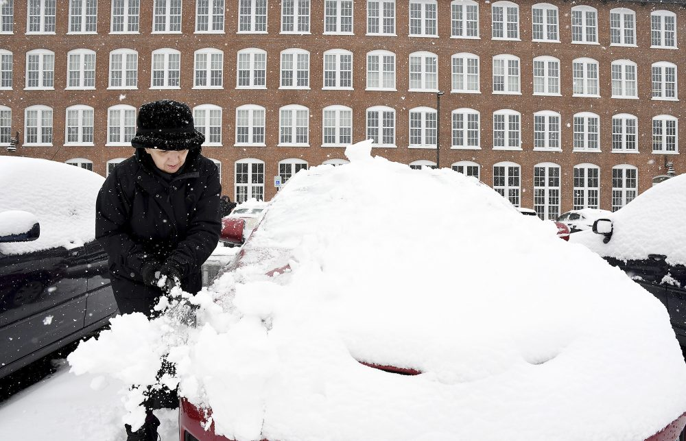 Sue Baker clears snow from her car at the Sterling Lofts apartments Tuesday,  in Attleboro, Mass. The area received several new inches of snow overnight.