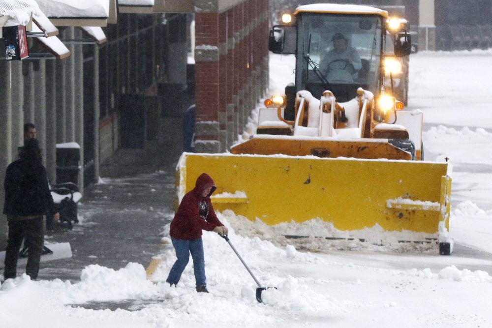 People clear snow in a shopping center after an overnight snowfall, Monday in Marlborough, Mass.