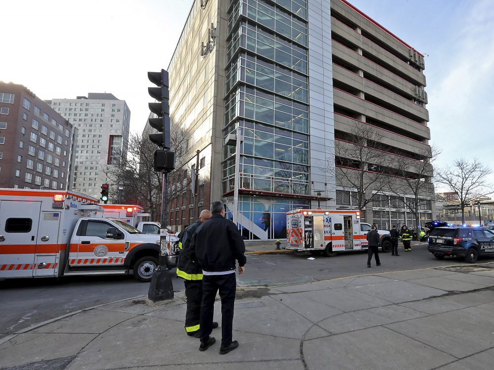 Emergency personnel at the Renaissance Park Garage in Boston, where a mother and two children were found dead on a sidewalk on Christmas Day.