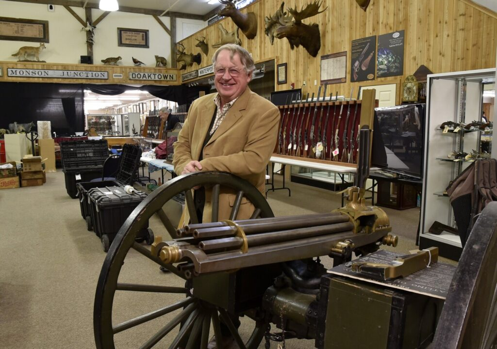 Auctioneer Jim Julia on Jan. 11, 2018, leans on an 1870s gatling gun that will be auctioned at his James D. Julia Auction Inc. business in Fairfield. The company Julia sold his auction house to has sued him for breach of contract.