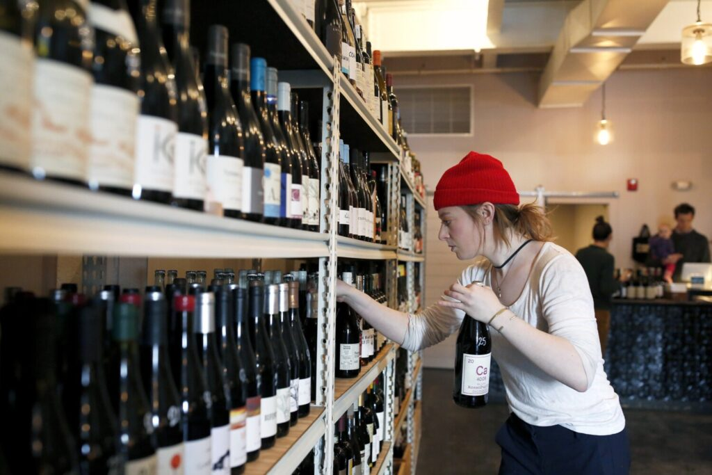 Lennie Newman stocks shelves at Maine & Loire wine shop on Tuesday. Severe tariffs on European wine, cheese and other products could devastate small businesses in Maine and across the U.S.