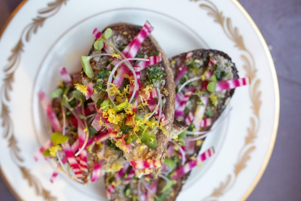 "The ""Fancy Toast,"" made with anchovy and shallot butter, chioggia beets and gremolata."