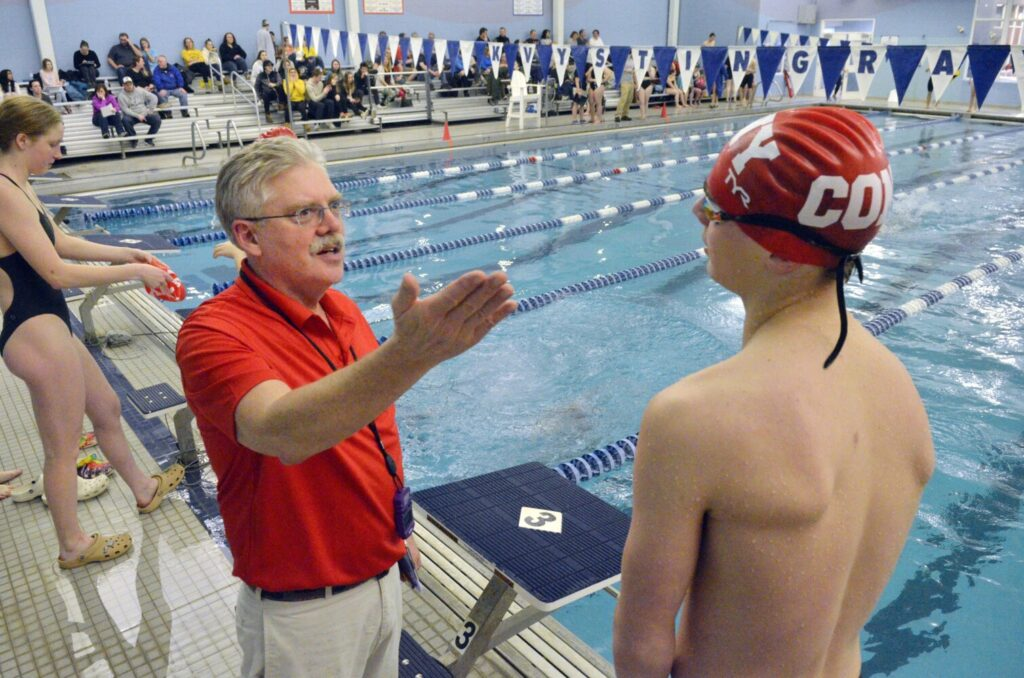 Cony coach Bob Johnston talks to Jack Begin during a meet on Friday at the Kennebec Valley YMCA in Augusta.