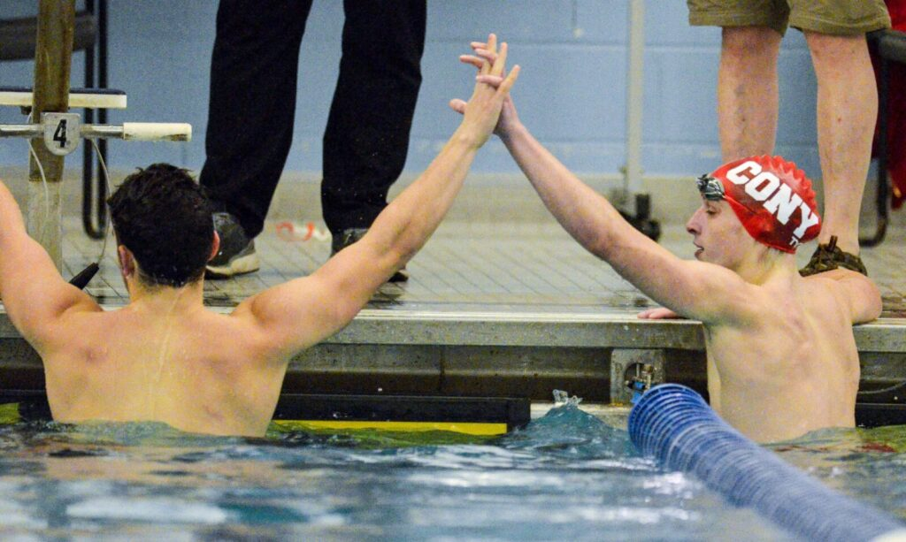 Waterville/Winslow's Eric Booth, left, and Cony's Gabe Biasuz clasp hands after competing in the 100-meter butterfly during a meet Friday at the Kennebec Valley YMCA in Augusta.