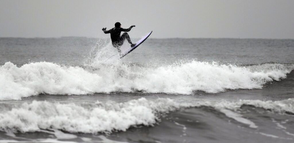A surfer catches some air as he rides a wave at Higgins Beach in Scarborough on Jan. 13. The world's scientists are warning that most of the world's oceans are speeding up.