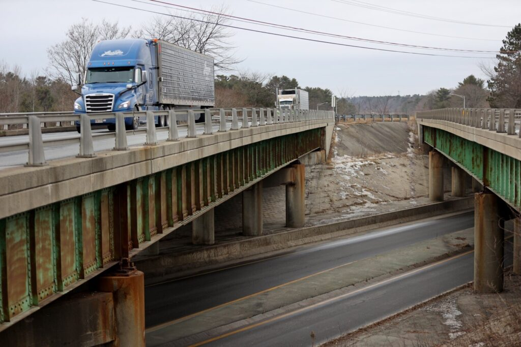Trucks travel north over the Interstate 295 overpass in Yarmouth Tuesday. The state's three-year highway construction plan costs $2.6 billion, but includes fewer projects than in previous years.