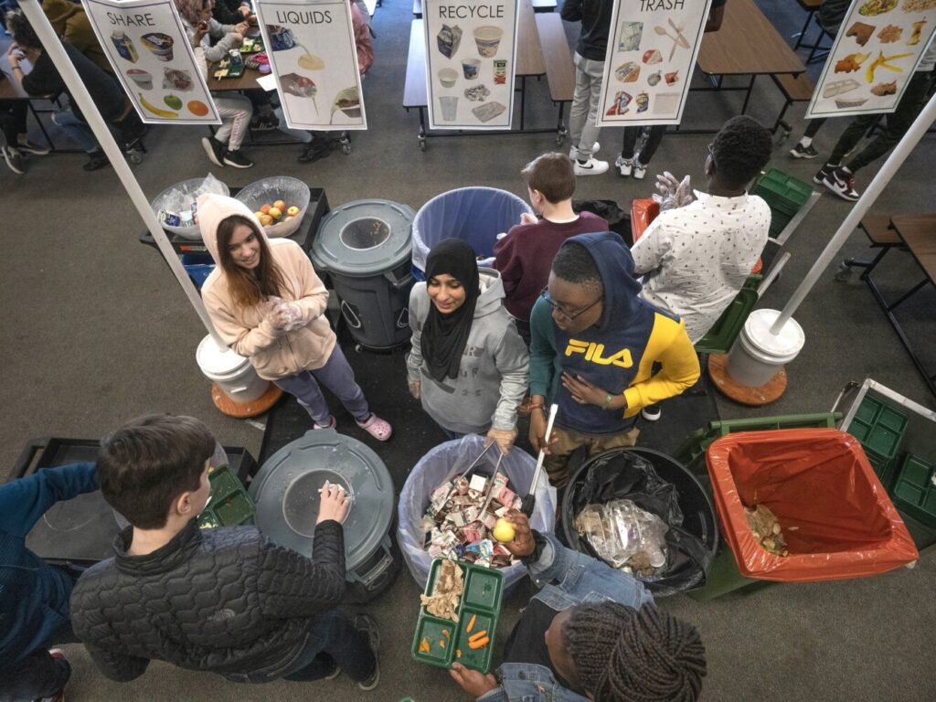 "King Middle School eighth-graders Avalon Kuzma, Kawther Hlail and Jean David Bisimwa, left to right, help students sort their lunch items as they clear their trays at the end of a lunch period Wednesday. Students who assist with the sorting are known as ""compost guardians"" at the Portland school."