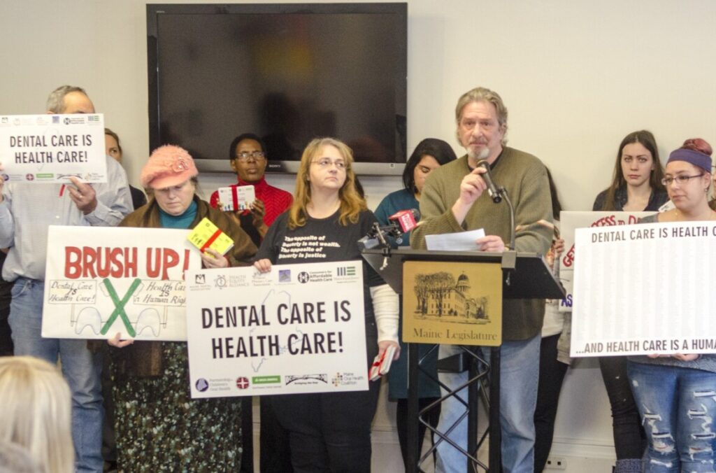 Kirk Robbins, 60, of Portland, from the Southern Maine Workers Center, speaks during a news conference by supporters of a dental health bill  on Thursday at the Maine State House in Augusta.