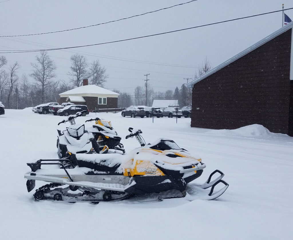 Snowmobiles await their student riders Thursday at Forest Hills Consolidated School in Jackman. For the past three years the schools have had no snow days.