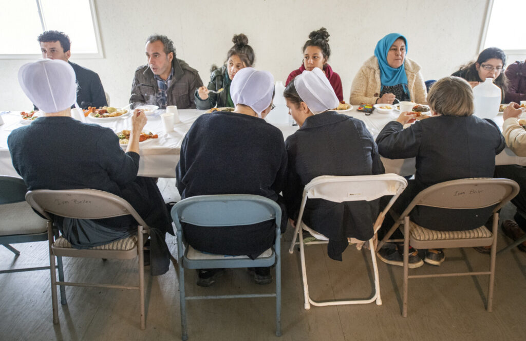 The Beiler family, in the foreground, eats with the refugees and visitors across from them. The event brings immigrants and neighbors together for a chance to share their stories and culture through food. (Paul Kuehnel/York Daily Record via AP)