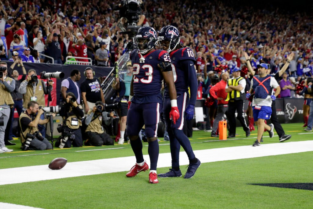 Texans running back Carlos Hyde, 23,  celebrates with DeAndre Hopkins after scoring a touchdown against the Buffalo Bills on Saturday in Houston. The Texans beat the Bills 22-19 in overtime in an AFC wild-card game.