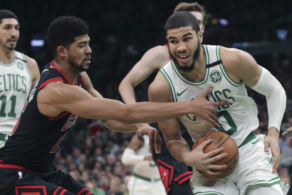 Chicago forward Chandler Hutchison , left, tries to steal the ball from Boston forward Jayson Tatum during the Celtics' 113-101 win Monday in Boston. Tatum finished with 21 points.