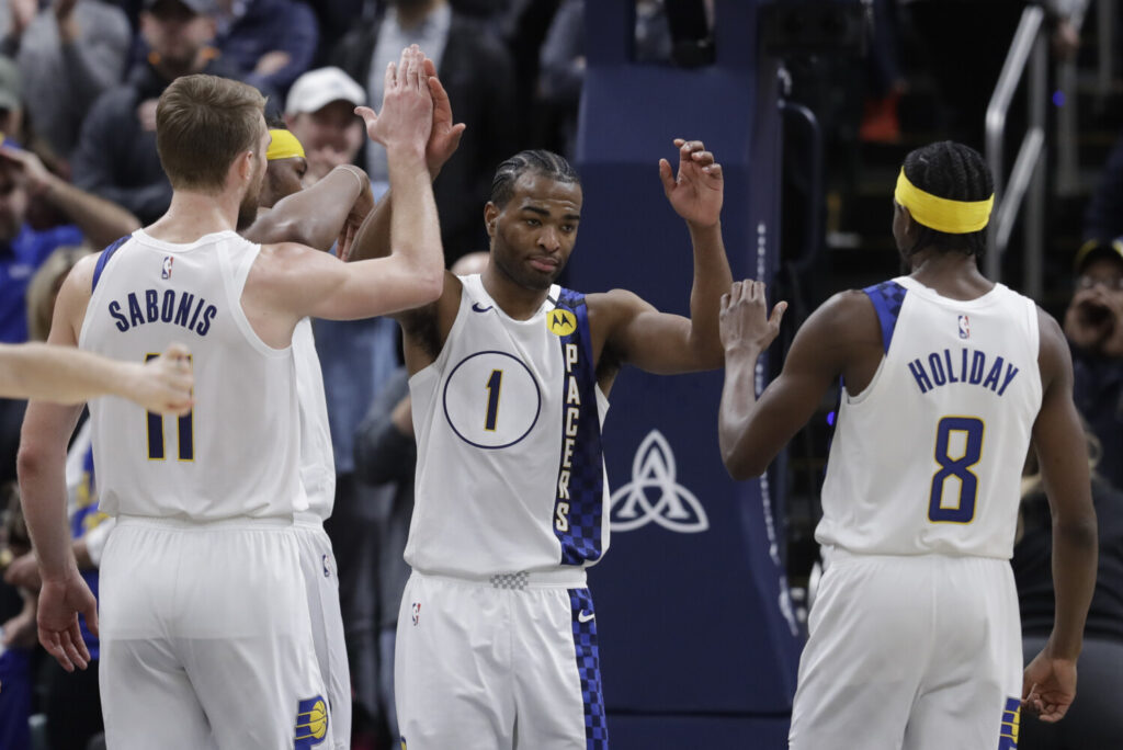 Indiana's T.J. Warren, center, is congratulated by Domantas Sabonis, left, and Justin Holiday for blocking the shot of Philadelphia's Tobias Harris in the second half of the Pacers 101-95 win Monday in Indianapolis.